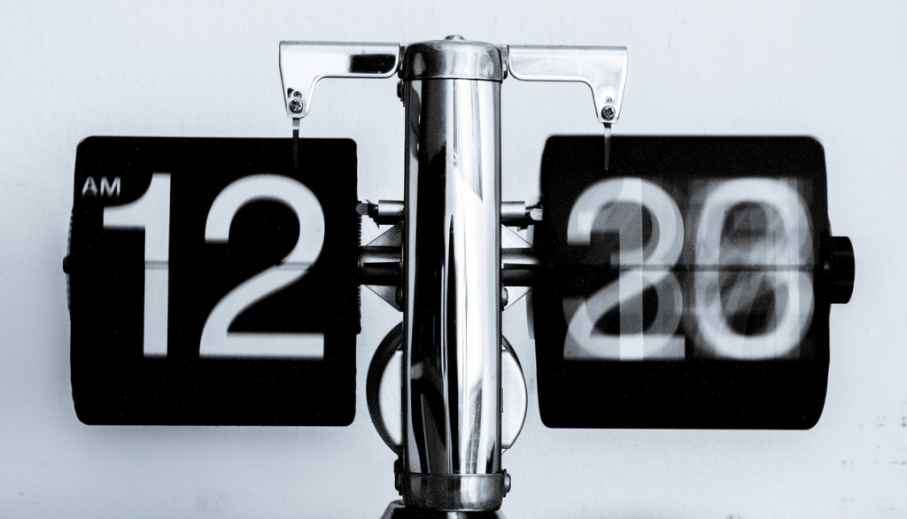 A small silver clock with number plates that spin to the correct time