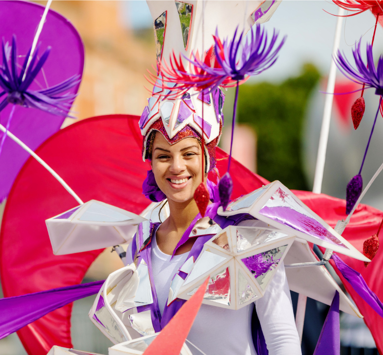 A lady dressed in bright festival clothing smiles at the camera