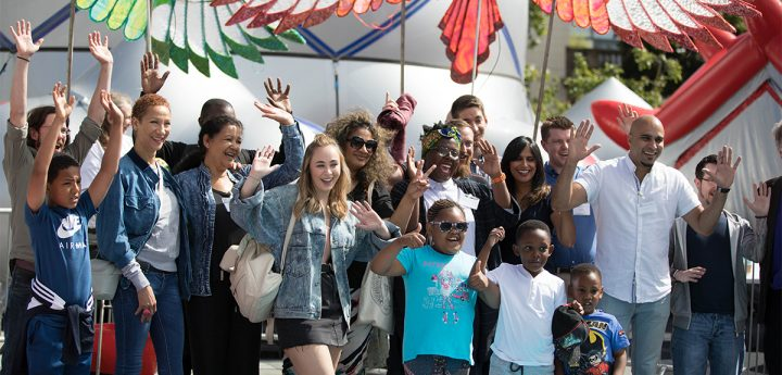 A group of people at a festival smile and hold their hands in the air to wave