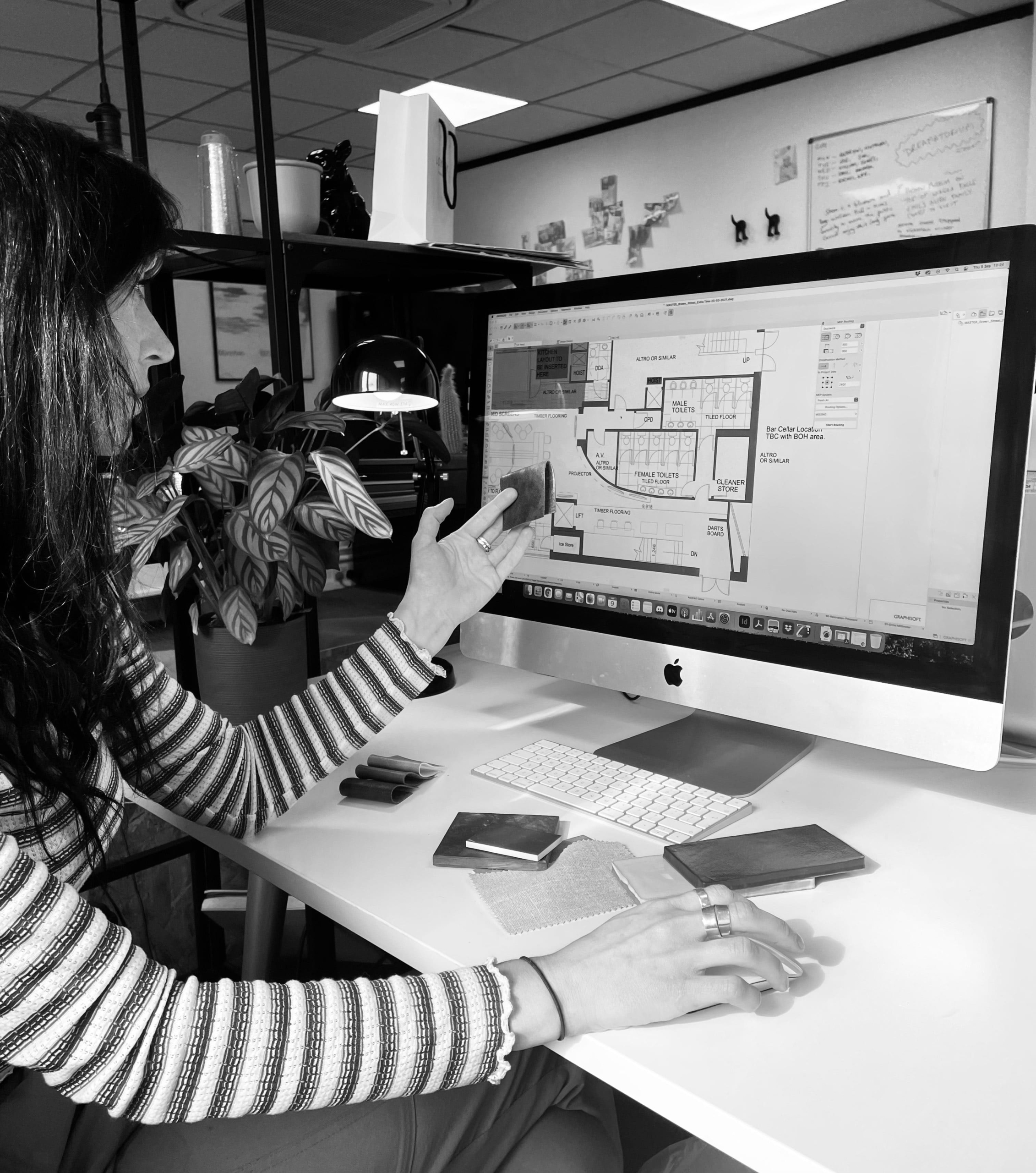 Head of Interior Design, Amanda, works on a project, she holds up a small fabric sample in her left hand and an apple mac screen shows a building plan