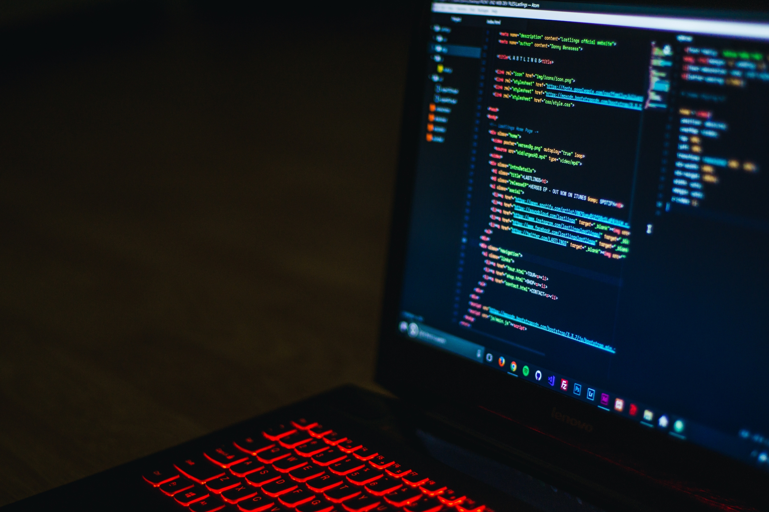 A laptop in the dark with code on screen